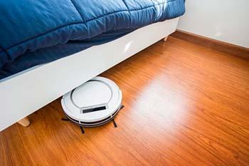 Robotstofzuiger reinigt onder een bed